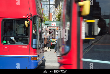 An Oxford street stall seen between two London buses, Oxford Street, London, UK - Stock Photo