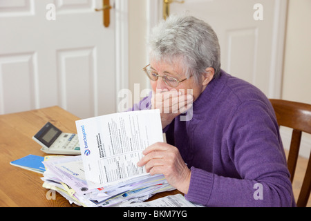 Worried senior woman retiree pensioner with a big pile of bills with hand over her mouth looking shocked at a large - Stock Photo
