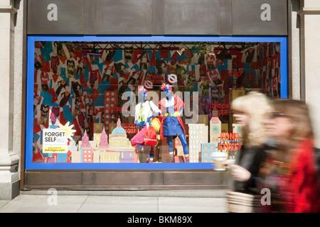 Shoppers walking past a shop window in Selfridges department store, Oxford Street, London UK - Stock Photo