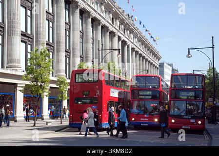 Buses outside Selfridges store, Oxford Street, London UK