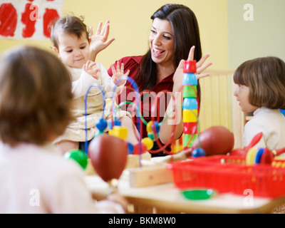 female toddler and 2-3 years girl playing in kindergarten. Horizontal shape - Stock Photo