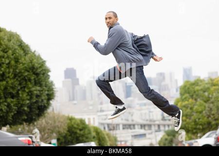 African American man running on urban street - Stock Photo