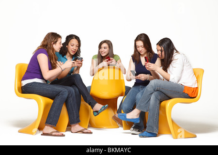 Five Teenagers sitting in chairs on phone texting and talking - Stock Photo