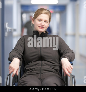 Woman patient in a wheelchair, in a hospital hallway. - Stock Photo