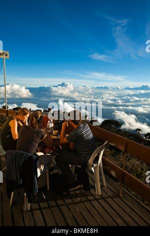 Hikers enjoy lunch above the clouds at Laban Rata resthouse, on Mt Kinabalu. Kinabalu National Park, Sabah, Borneo, - Stock Photo