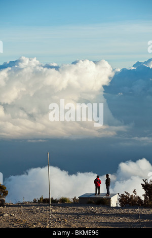 Hikers look out over the clouds from Laban Rata, on the Mt Kinabalu summit trail. Kinabalu National Park, Sabah, - Stock Photo