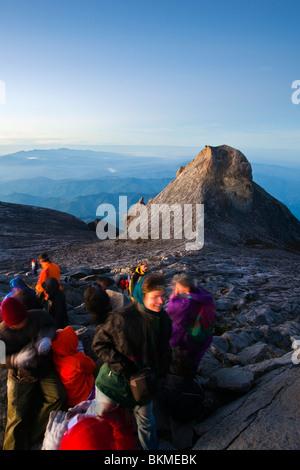 Climbers at Low's Peak, on the summit of Mt Kinabalu at dawn. Kinabalu National Park, Sabah, Borneo, Malaysia. - Stock Photo