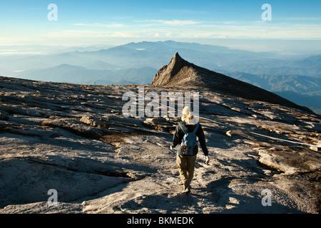 Hiker on Mt Kinabalu with South Peak in the background. Kinabalu National Park, Sabah, Borneo, Malaysia. - Stock Photo