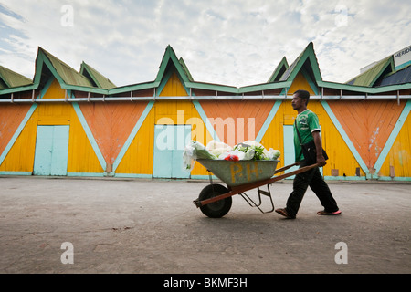 Man pushing wheelbarrow full of produce, in front of the Filipino Handicraft Market. Kota Kinabalu, Sabah, Borneo, - Stock Photo
