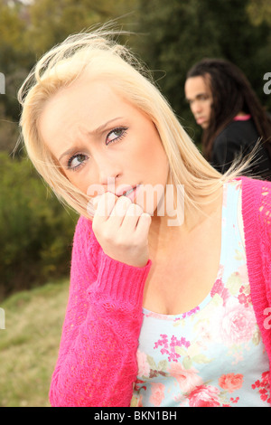 Young blonde woman in 20's looks expressive as dread lock haired boyfriend walks away - Stock Photo
