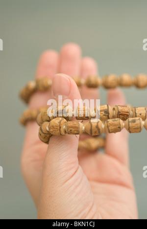 Woman hand holding 108 Tibetan Wooden Yoga Meditation Prayer Beads Mala Necklace - Stock Photo