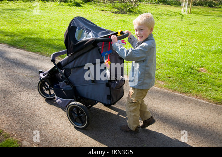 Baby being pushed in a pram / push chair being pushed by a small boy, aged five years old. - Stock Photo