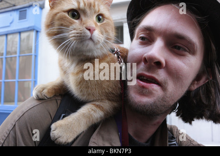 Big Issue vendor with his pet cat `Bob' stationed upon his shoulder,snapped casually walking down Shelton St,Covent - Stock Photo