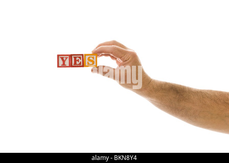 Man holding children's blocks that spell 'YES' - Stock Photo