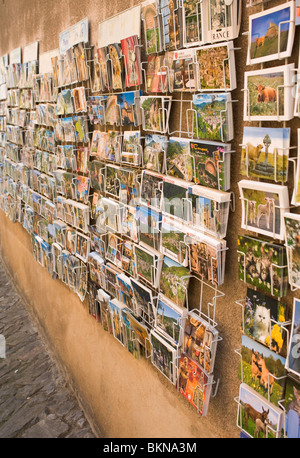Postcards On Sale in Racks Outside a Gift Shop in Conques Aveyron Midi-Pyrenees France - Stock Photo
