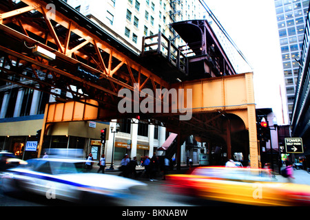 CARS PASSING AND PEOPLE CROSSING WELLST STREET UNDER EL TRAIN IN DOWNTOWN, CHICAGO, ILLINOIS, USA DURING AFTERNOON - Stock Photo