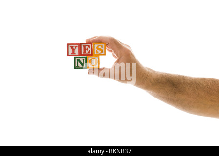 Man holding children's blocks that spell 'YES' 'NO' - Stock Photo