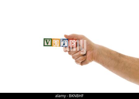 Man holding children's blocks that spell 'VOTE' - Stock Photo