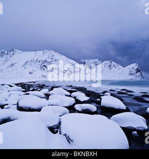 Snow covered rocks at Unstad beach, Vestvågøy, Lofoten islands, Norway - Stock Photo