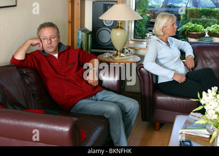Unhappy couple sitting on couch back to back - Stock Photo