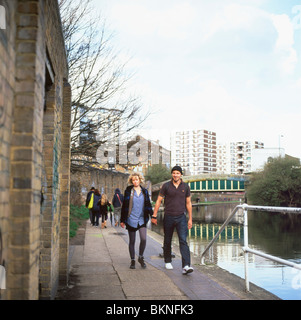 A couple holding hands, strolling along the Regents Canal between Camden and Hoxton, London England UK - Stock Photo