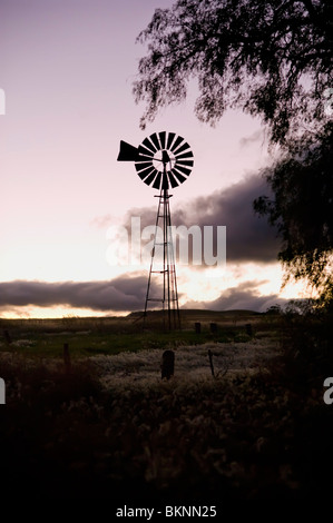 Windmill silhouetted against clouds - Stock Photo