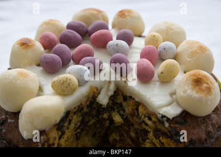 Close-up of a simnel cake with a large slice missing, England. - Stock Photo