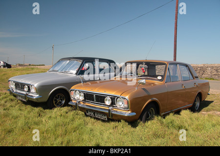 Two 4 door Ford Cortina Mark II classic cars parked close to the Hook lighthouse on the Hook Penisula, Wexford, - Stock Photo