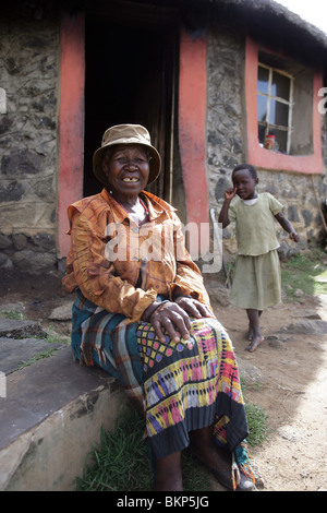 Woman and grandchild on the steps of a traditional Basotho house made of stone in Lesotho - Stock Photo