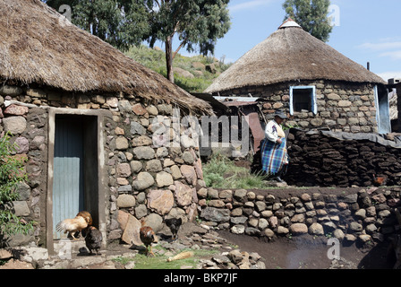 Traditional Basotho rondoval house made of stone with a thatch roof in Lesotho, Southern Africa - Stock Photo