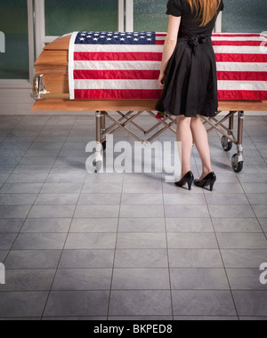 Paying Respects To The Deceased With An American Flag Draped Over The Coffin - Stock Photo