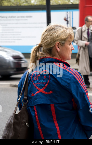 A woman crossing the road wearing a jacket sponsored by the London Marathon 2010 - Stock Photo