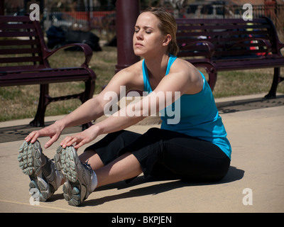 young woman stretching before running - Stock Photo