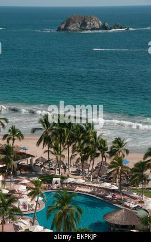 Hotel swimming pool and Pacific Ocean beach at Ixtapa Guerrero Mexico - Stock Photo