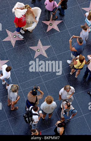 Stock photograph of overhead view of a street performer dressed as an angel working on the Walk of Fame Hollywood - Stock Photo