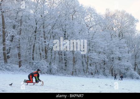 Sleeende jongen in een besneeuwd landschap; Sledge-riding boy in a snow covered landscape - Stock Photo