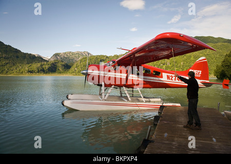 Person waves to a Dehaviland Beaver floatplane as it leaves the Redoubt Bay Lodge Southcentral Alaska Summer - Stock Photo