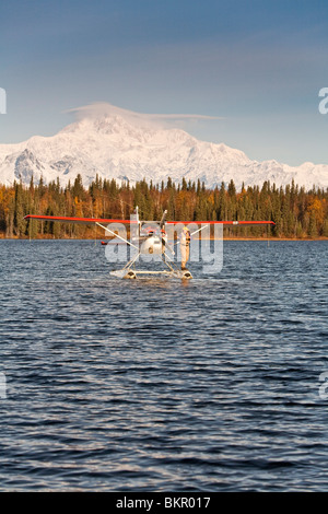 Flyfisherman fishing off of the float of a Cessna 185 floatplane on a lake with Mt. Mckinley and Alaska Range iin - Stock Photo