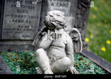 Stone cherub on a grave in Highgate Cemetery. - Stock Photo