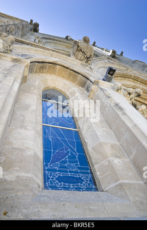 Looking up at an old church, focusing on a stained glass window, from the outside. Church of our Lady, Guelph, Ontario, - Stock Photo