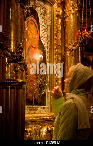 Russia, St.Petersburg; Before an Orthodox Ceremony begins, a girl prays in front of the Madonna at Vladimirsky Cathedral. - Stock Photo
