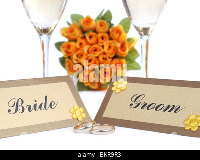 Bride and Groom name cards, wedding rings, two white wine glasses and Bride's yellow rose bouquet in the background - Stock Photo
