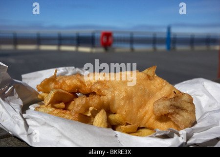 traditional english fish and chips in paper wrapper on a pier at the seaside england uk - Stock Photo