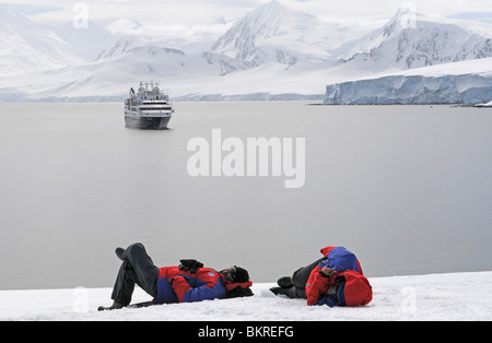 Tourists lying on the waterfront in Damoy Point, Wiencke Island, Palmer Archipelago, Antarctica - Stock Photo