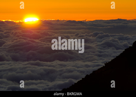 The sun rises over clouds that hide the Pacific Ocean, from the summit of Haleakala volcano, Maui, Hawaii - Stock Photo