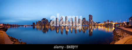 False creek framed by the Vancouver Seawall reflects the lights of Yaletown apartment complexes and BC Place Stadium - Stock Photo