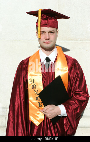 Young male graduate poses in cap and gown. - Stock Photo