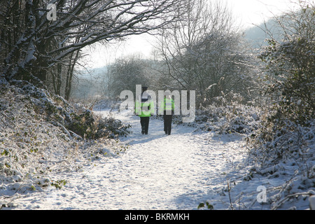Two community police officers walking along a snow covered path at Bathpool, Kidsgrove, Stoke-on-Trent, Staffs - Stock Photo