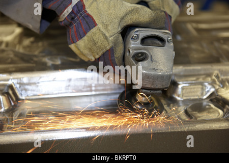 man using a angle grinder on metal surface with sparks - Stock Photo