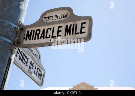 Street sign indicating the junction of Miracle Mile and Ponce de Leon, Coral Gables, Miami Florida - Stock Photo